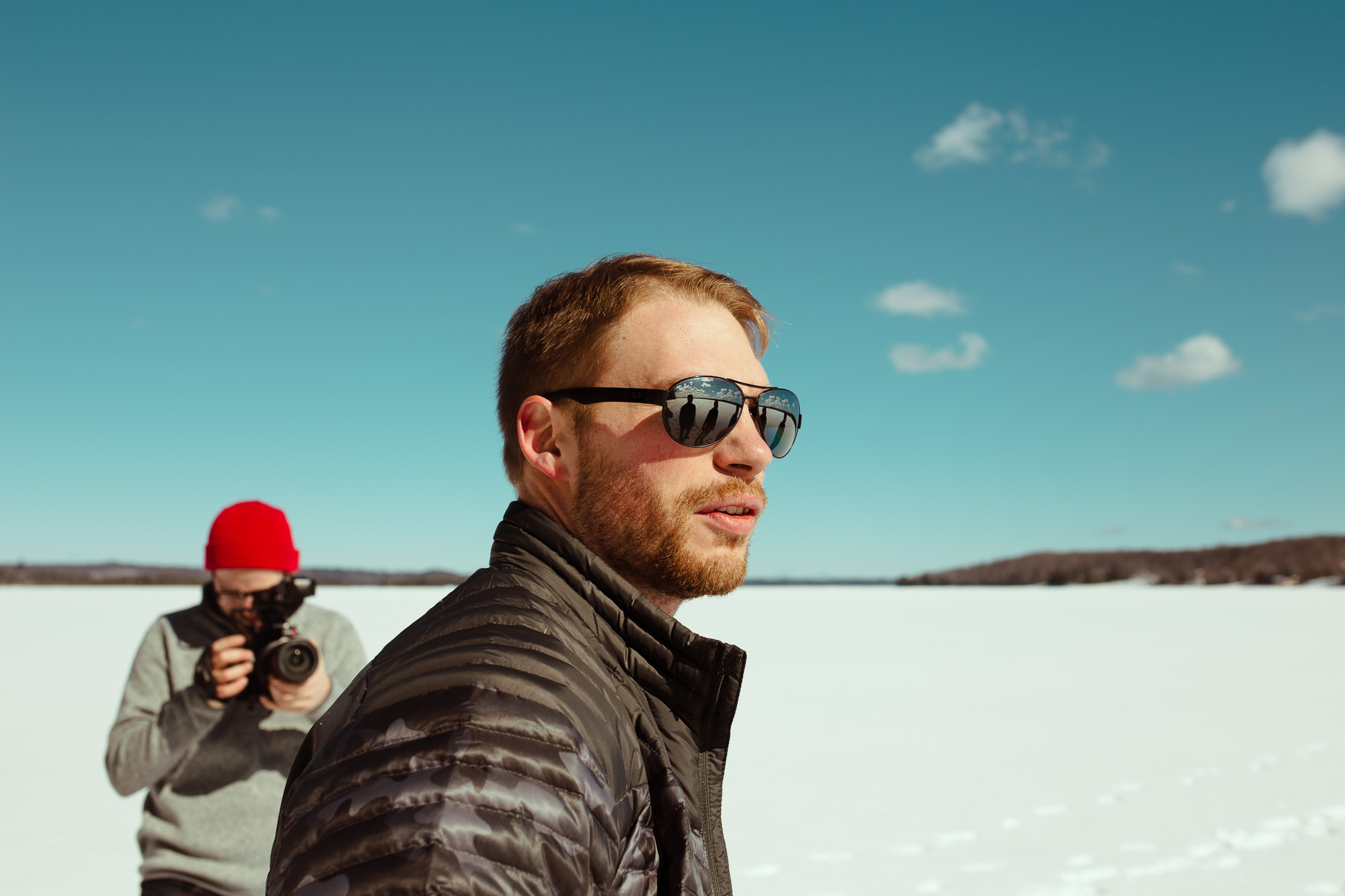 Man taking photo of another man in sunglasses