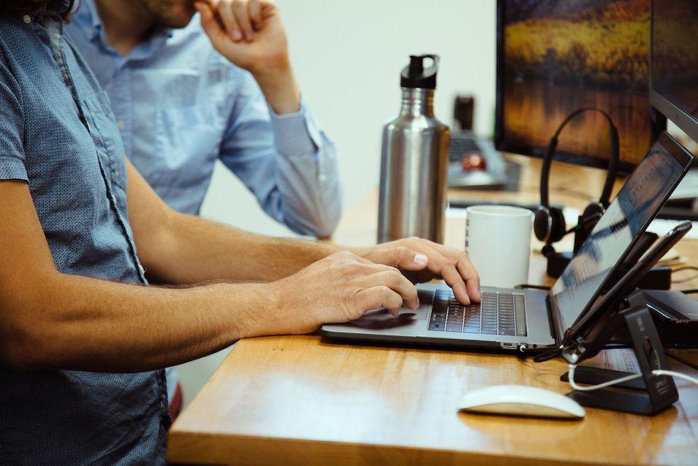 developer typing on macbook pro at desk