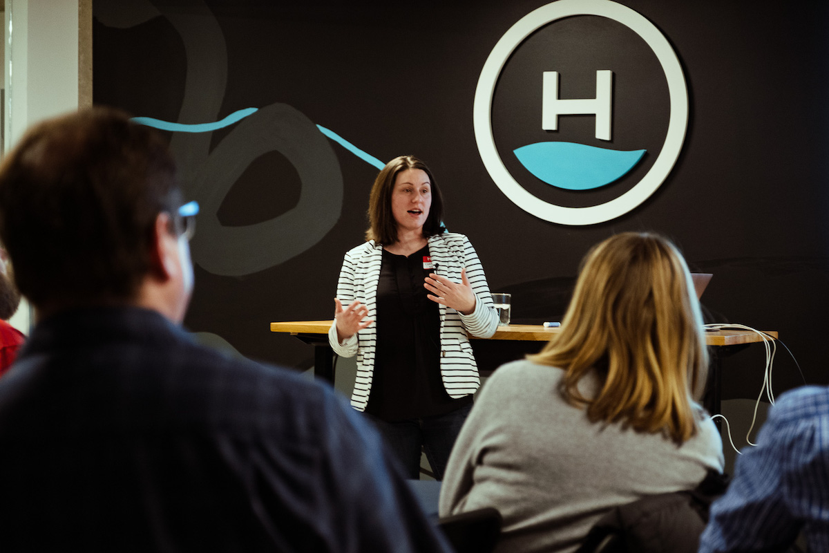 woman presenting to community at headway office