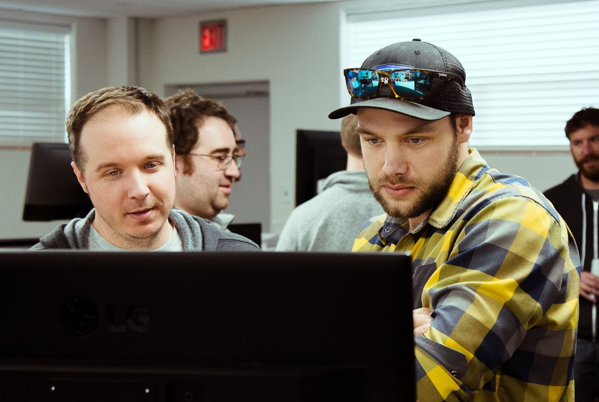 two men discussing react project on computer screen