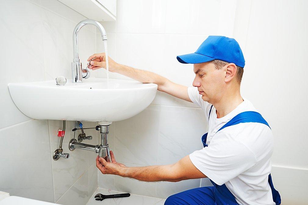 Plumber checking sink tap.