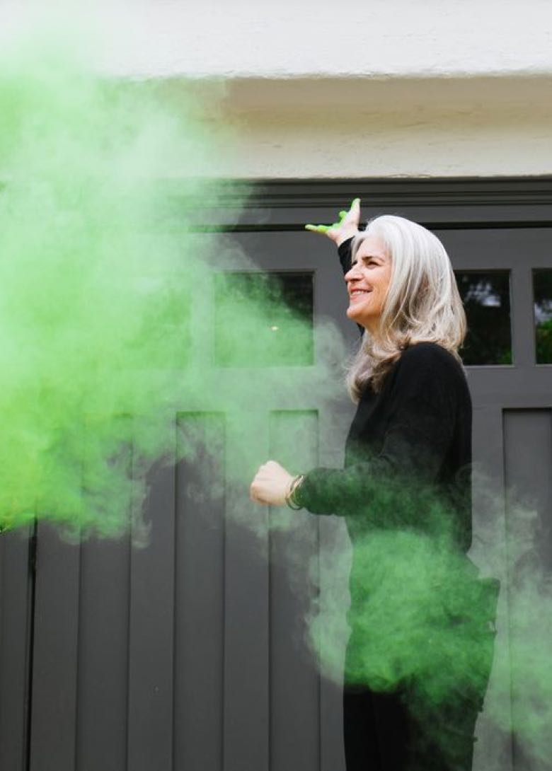 Anna Scott smiling with a cloud of green smoke