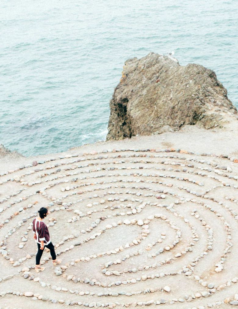 Woman walking through stone maze beside the ocean
