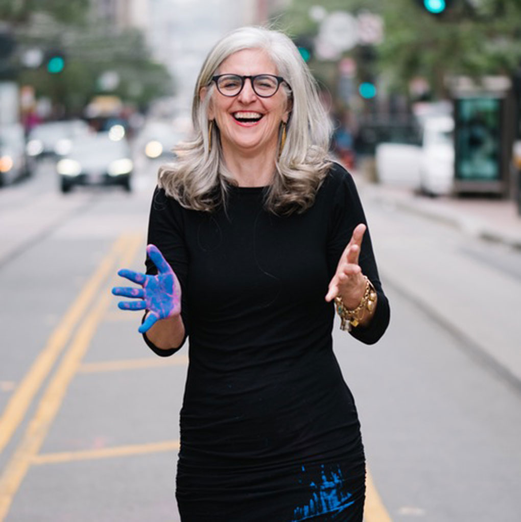 Anna Scott laughing with blue pigment on her hand and dress