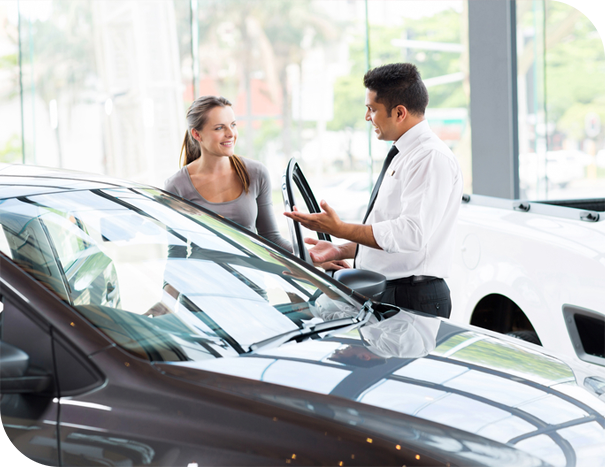 auto dealer showing woman a new car