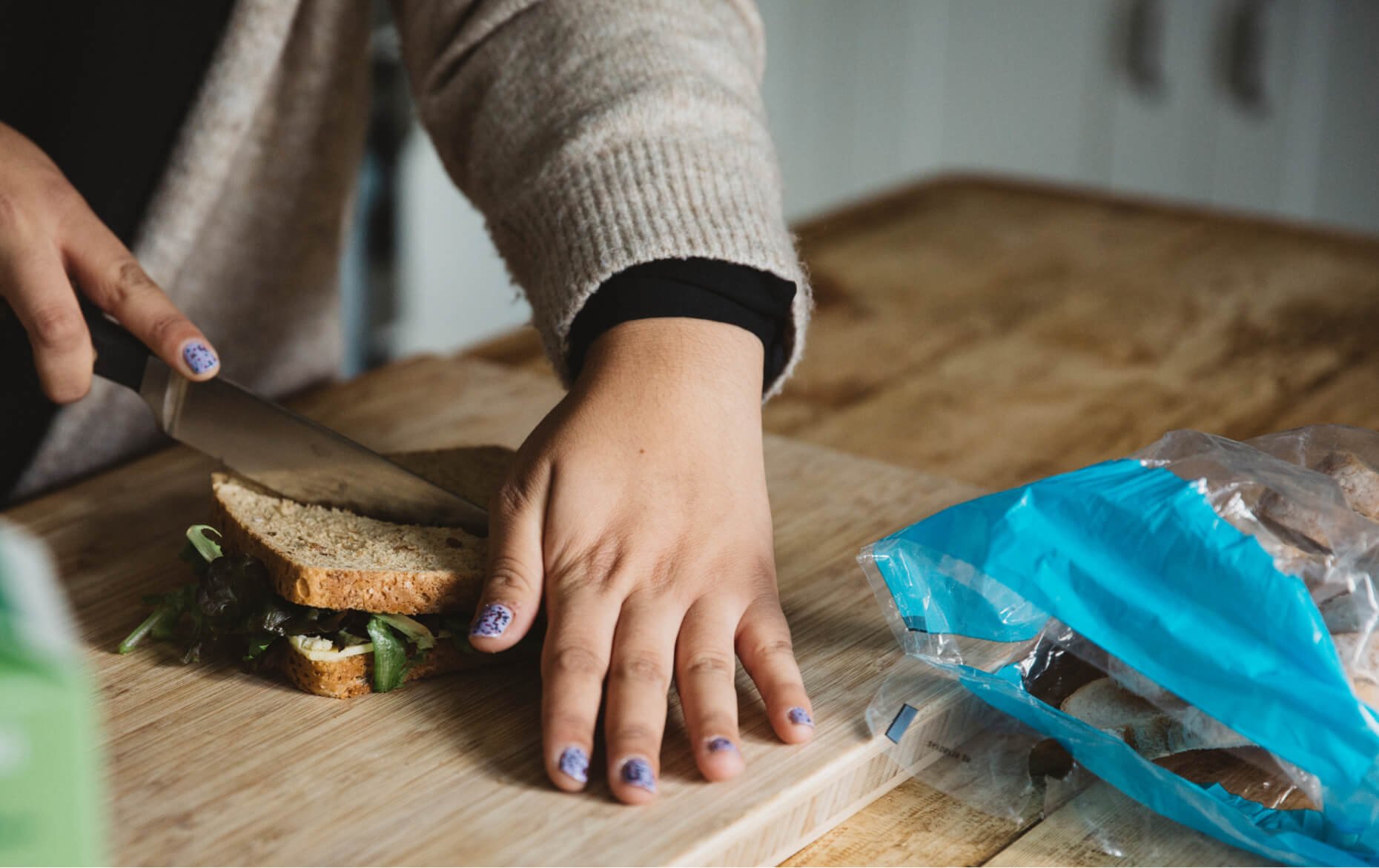 Carer cuts a sandwich on a wooden chopping board