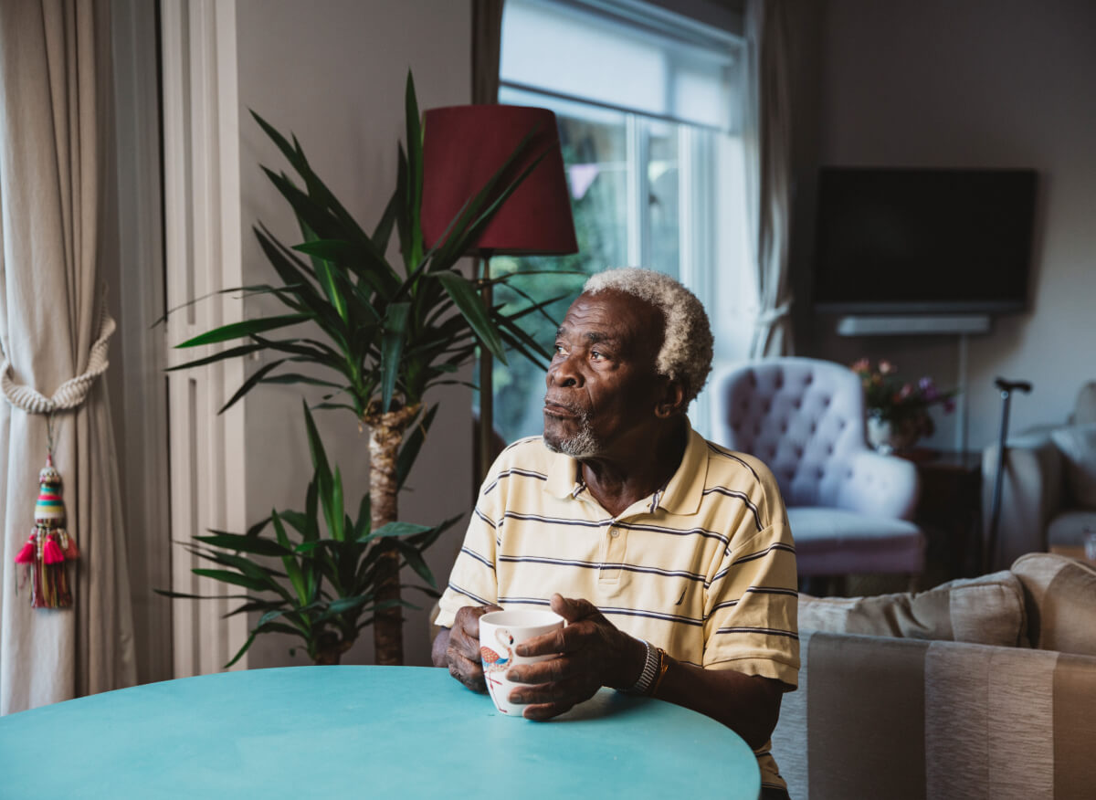 Elderly man sits at table and looks out of the window
