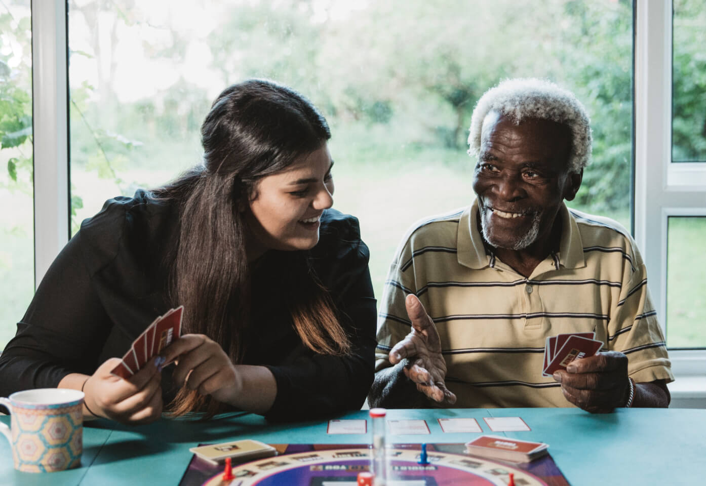 elderly man and carer play board games