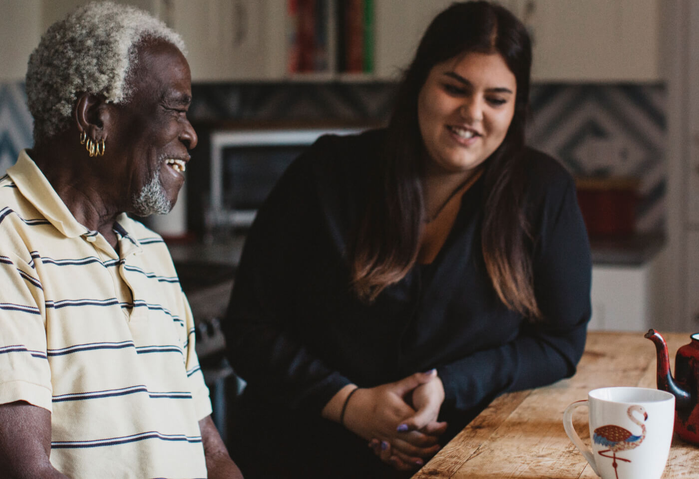 Elderly man with earrings sits at wooden table with a carer smiling