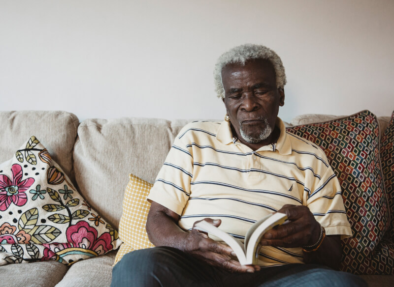 elderly man reads a book on a beige sofa, next to a floral cushion