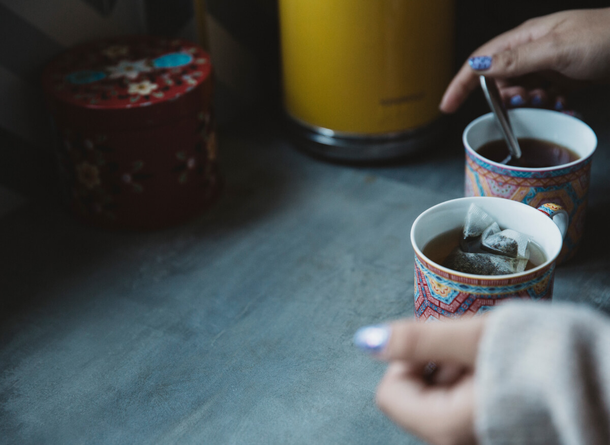 Carer makes two cups of tea in brightly coloured mugs, on a dark wooden surface
