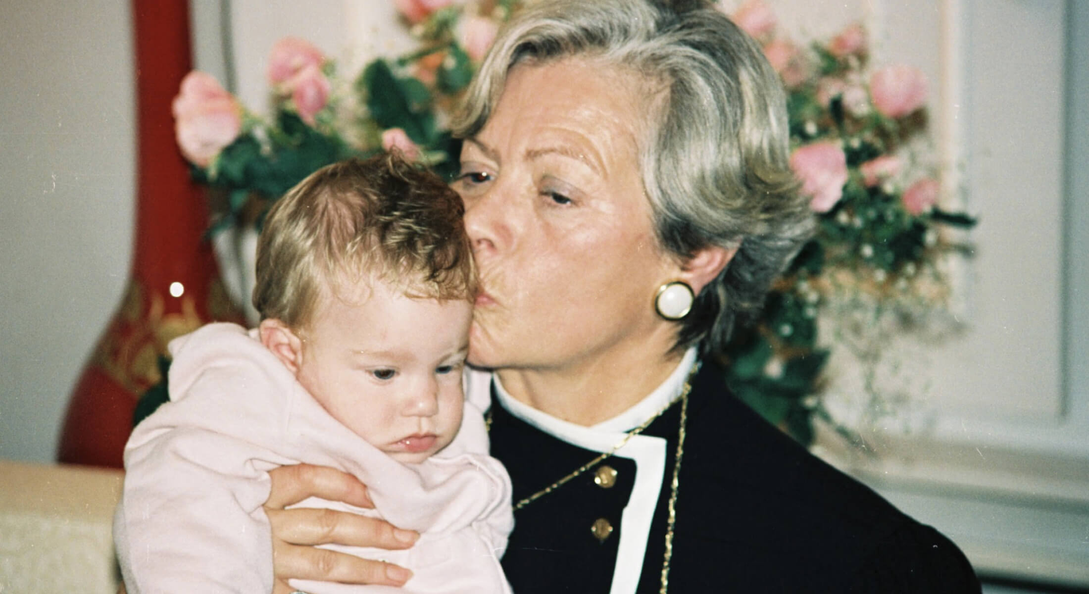 Photo of an elderly woman holding a small baby and kissing it's head