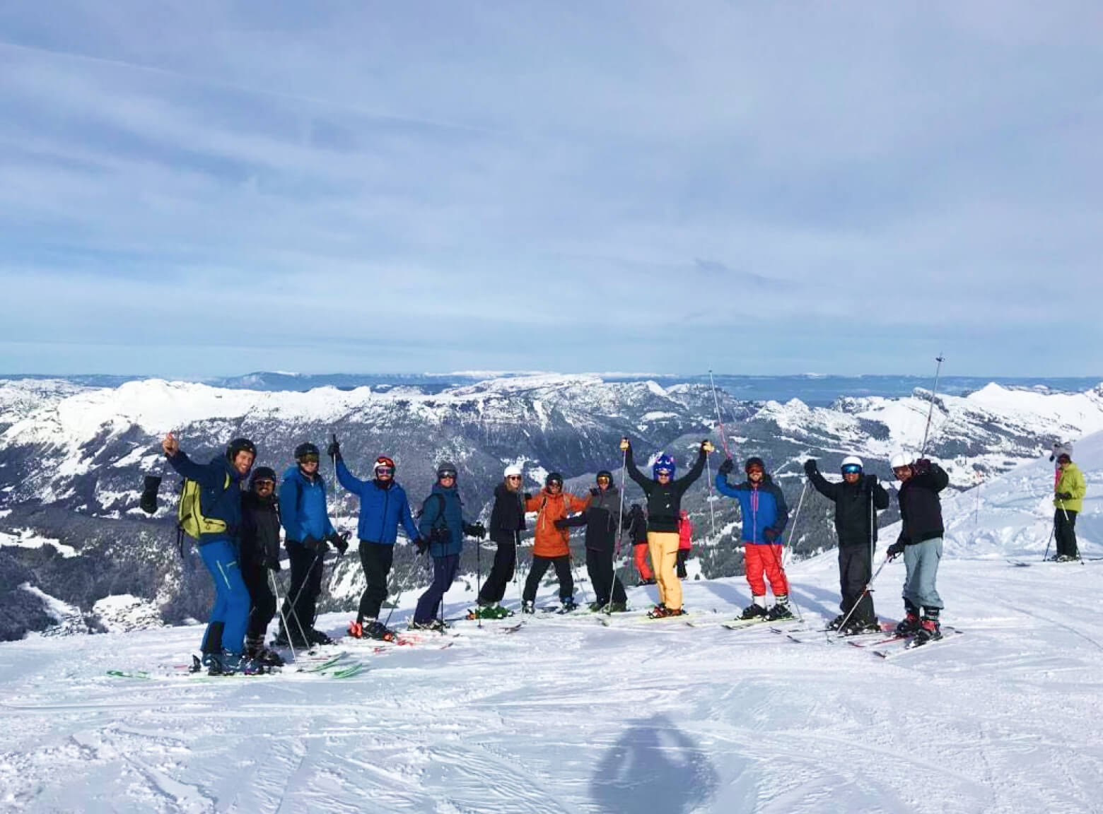 The birdie team on the annual ski trip with a mountain view and brightly dressed skiiers