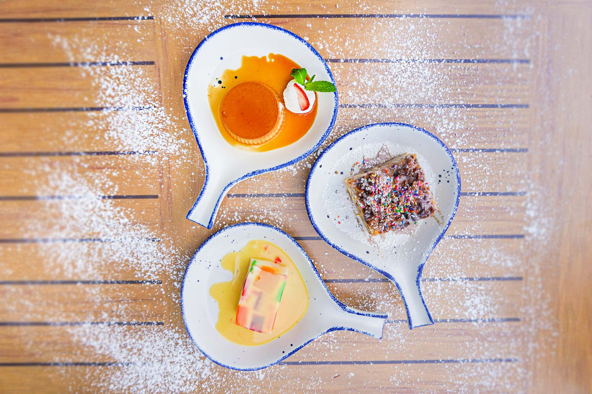 three desserts on a wooden table with powered sugar
