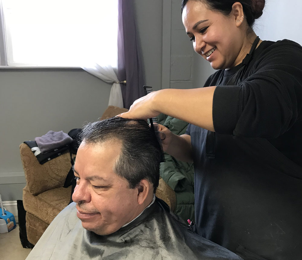 A resident at the Lighthouse getting a haircut from a volunteer