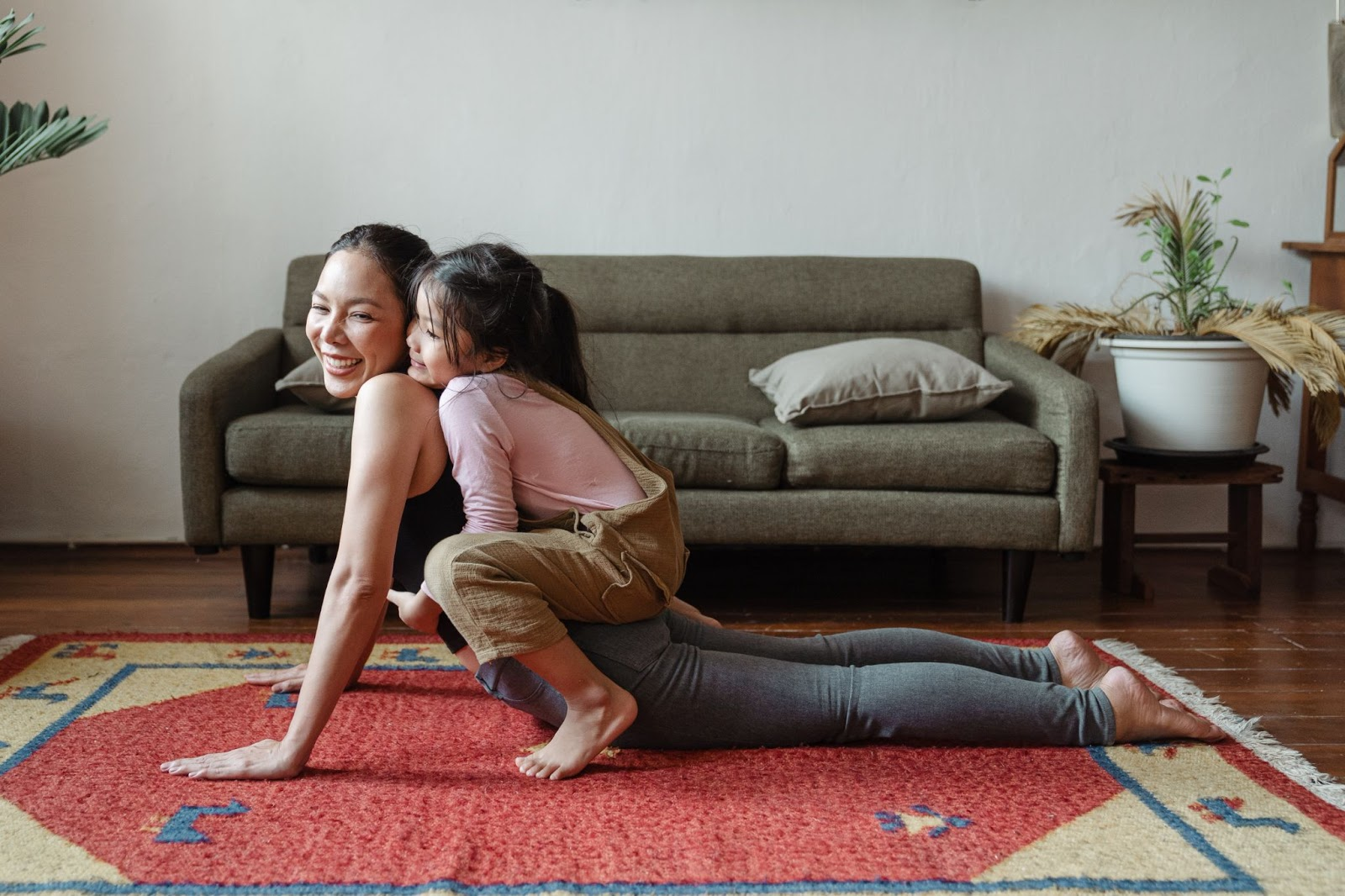 mother and daughter practice yoga while working from home