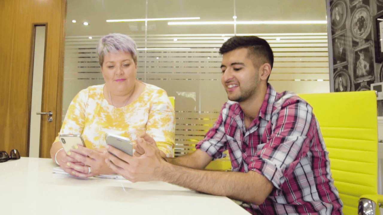 Care worker and birdie staff member work at a white table in a yellow office