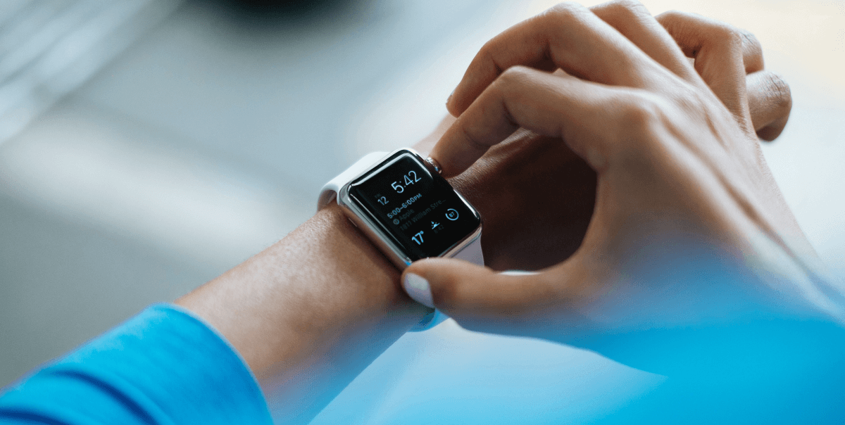 Woman in blue top uses a smart applewatch