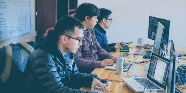 devs working on computers at at a wooden desk wearing coats with a whiteboard behind them