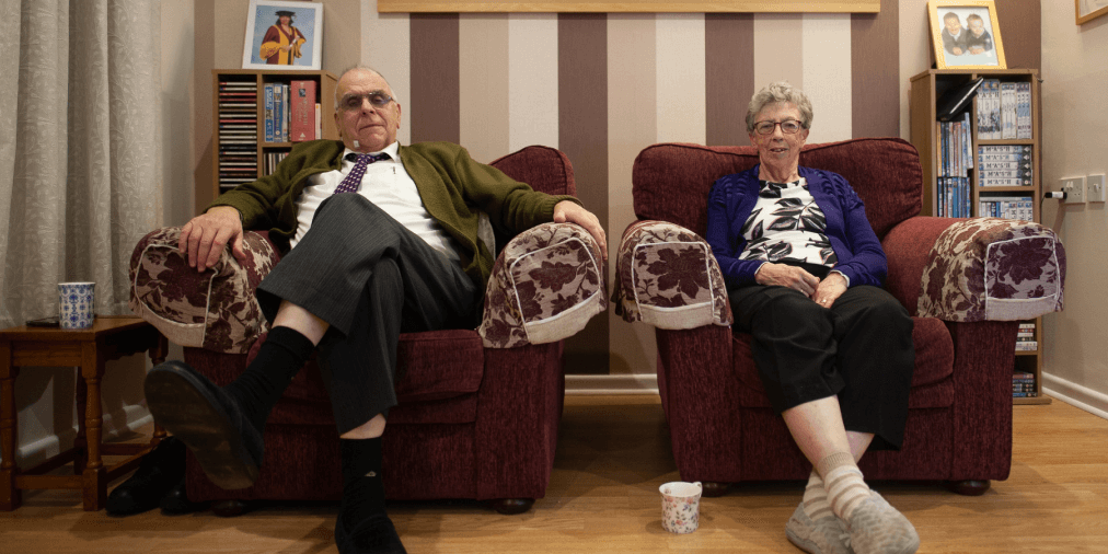 Elderly couple sit in maroon armchairs with patterned arms, in front of a striped background wallpaper. In the background are photographs of children and grandchildren. The woman has a floral mug on the floor by her feet. Both are wearing slippers but dressed for everyday life.