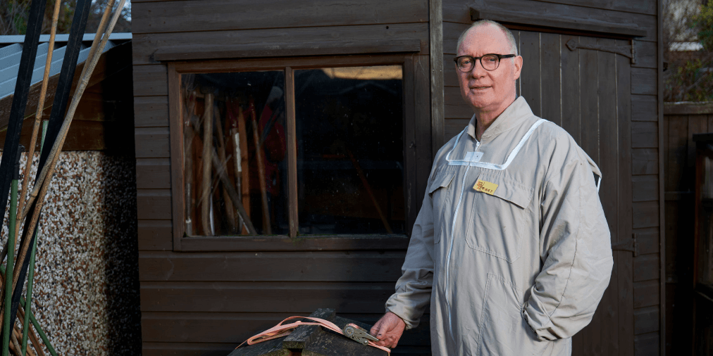 Man with glasses stands in front of a shed, holding a tightening cable, wearing a grey boilersuit