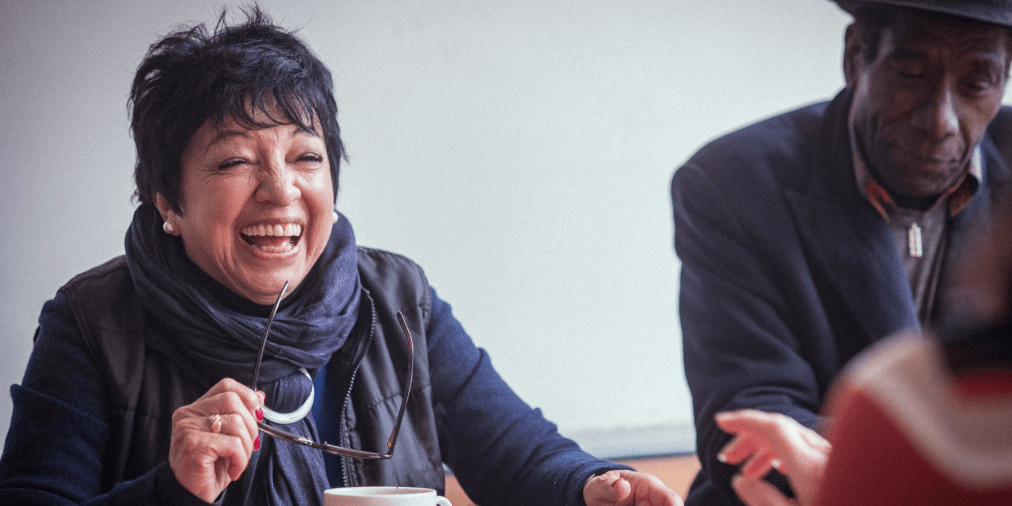 Woman in blue jumper with short black hair and pearl earrings holds her glasses in her left hand while laughing at a person opposite her. A black man in a hat is sitting next to her