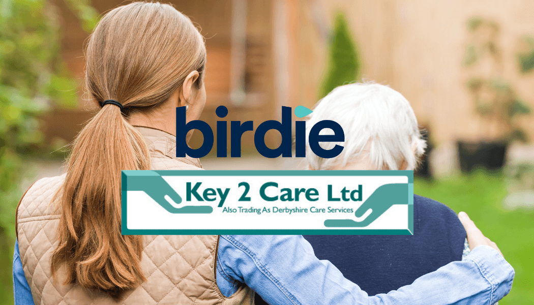 Young woman and old woman walk away from camera. Young woman has a quilted jacket and denim shirt. She has her arm around the old woman with grey short hair. On top of the image is the Birdie Logo and the Key To Care logo