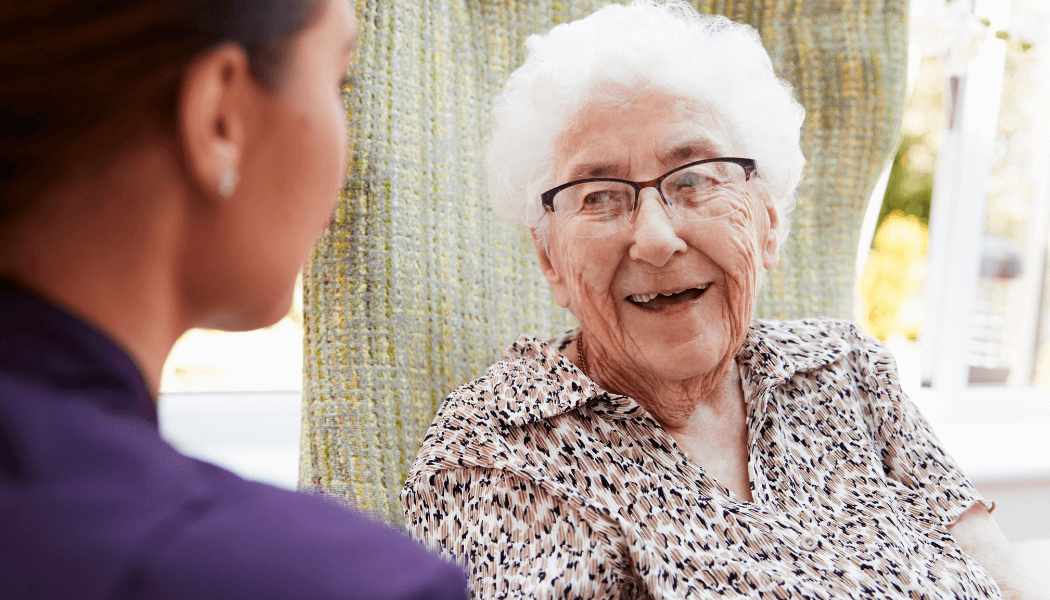 elderly woman with white hair and a patterned blouse with half framed glasses smiles at a woman with brown hair and a purple tunic