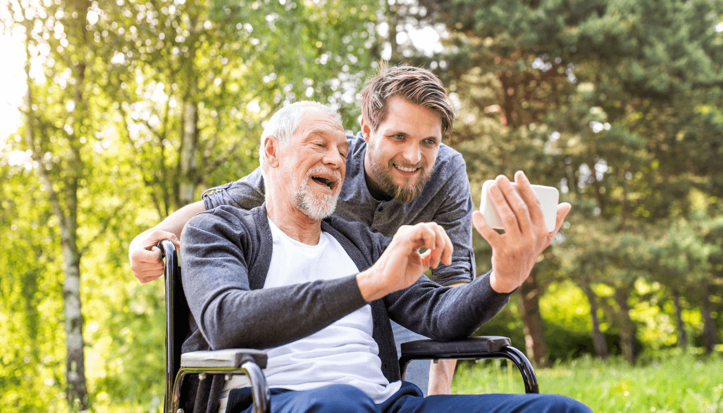 Male carer with beard poses for a photo with an elderly man in a wheelchair who is holding a white phone in his outstretched hand and smiling.