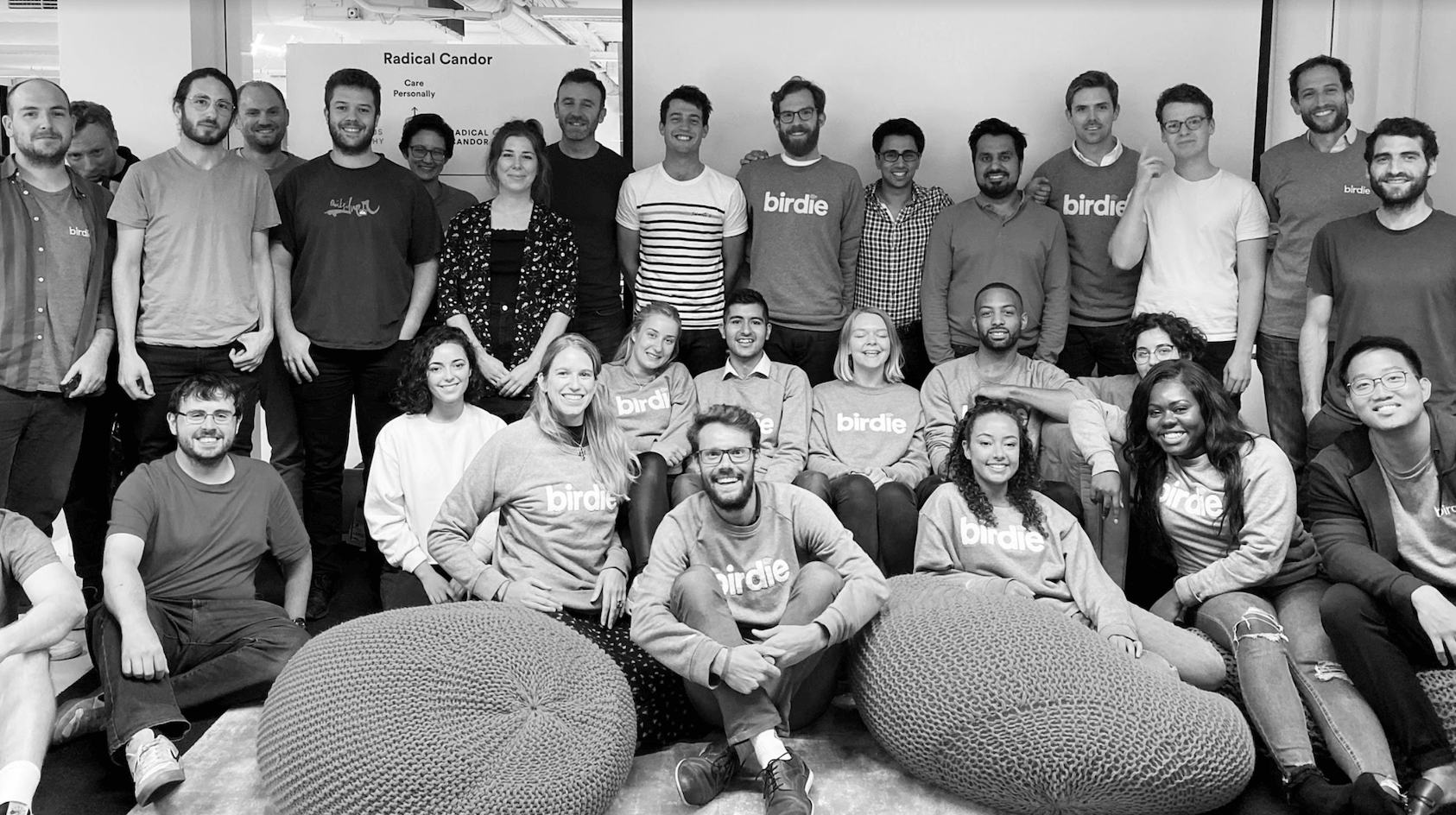Team of people stand in office, in front of radical candor poster, wearing grey birdie jumpers. There are beanbags in the forefront