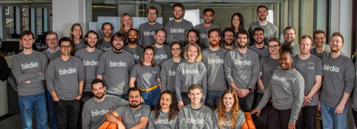 Team photo of Birdie staff standing in front of a glass wall and sitting on an orange sofa. The team wear matching grey sweatshirts with Birdie emblazoned on their chests.