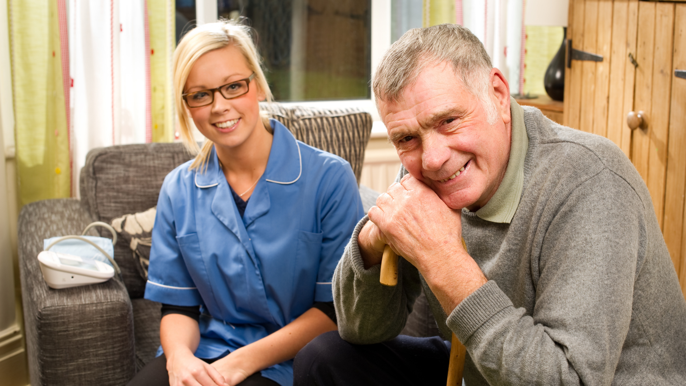 Woman in blue tabard sits with a man in his home, he is leaning on a cane. boh are smiling