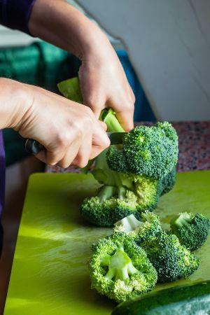 Person chopping broccoli to prepare broccoli rice