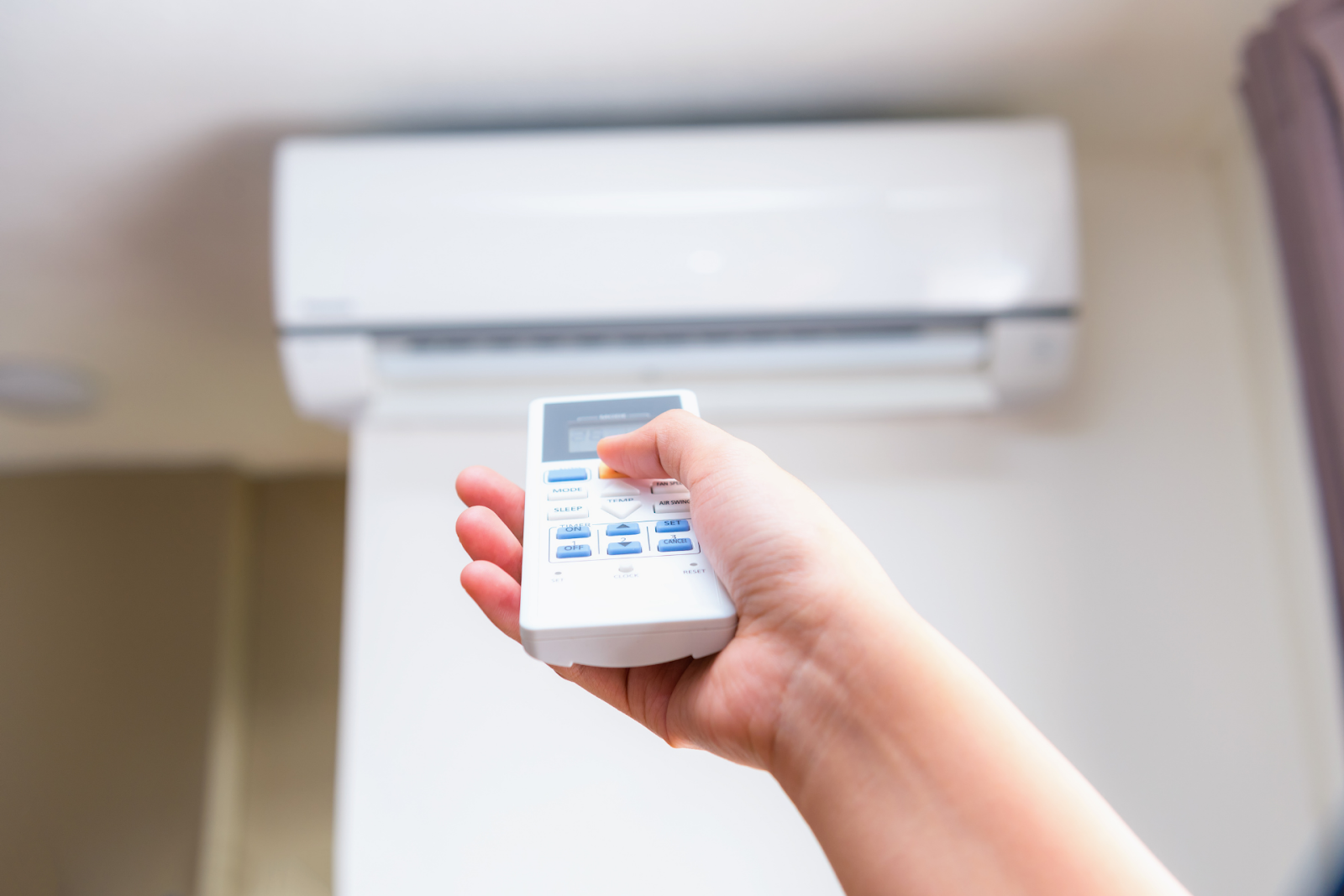 person turning on air conditioner
