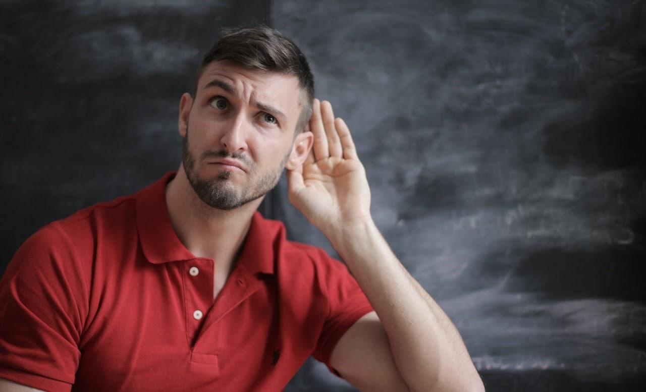 man in red polo shirt listening sitting near chalkboard