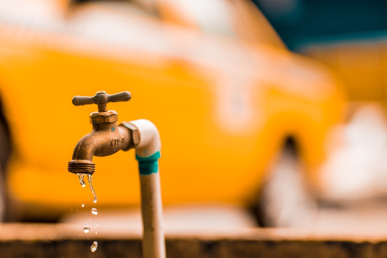 faucet leaking outside yellow car in the background