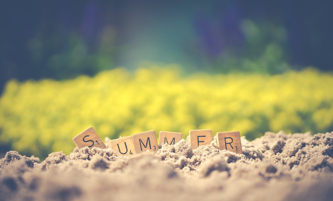 summer scrabble pieces in sand with green background beach