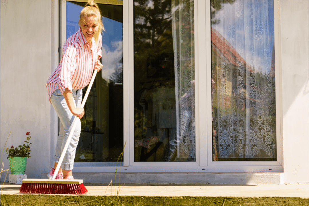 woman cleaning back porch with a broom sunny day summer reflection blond hair striped shirt