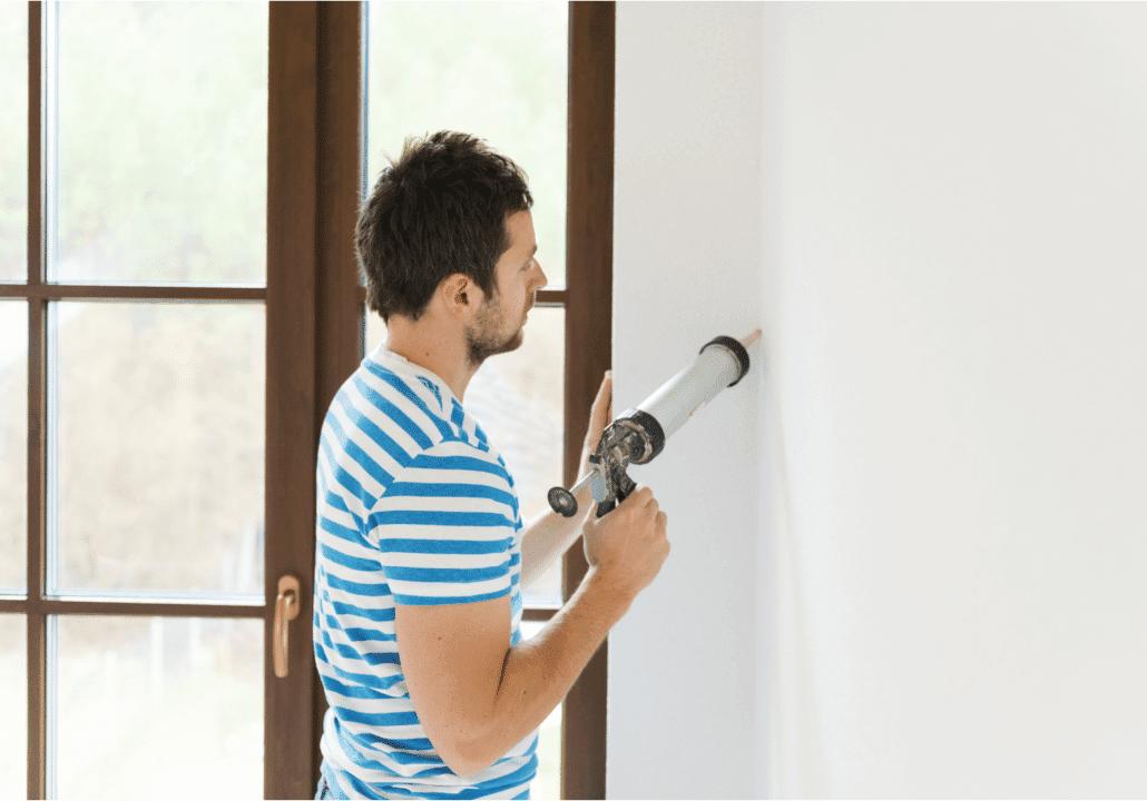 man striped blue shirt caulking gun fixing wall gap brown door windows concentrating