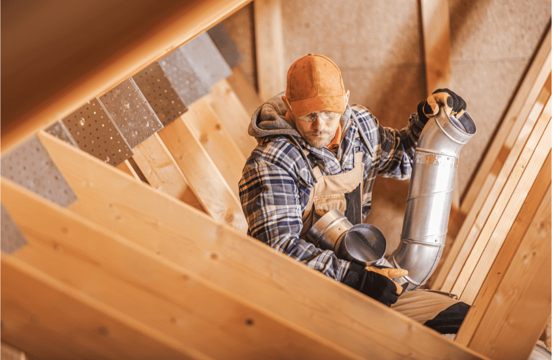 man installing attic fan ducts wooden frame plaid work shirt gloves concentration construction