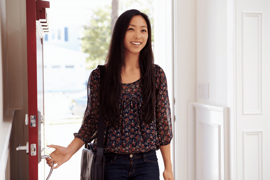 woman open door happy expression blouse red white jeans smiling long hair