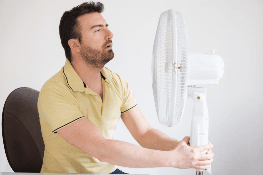 man overheating yellow polo shirt holding fan in face cooling down hot air conditioner broken