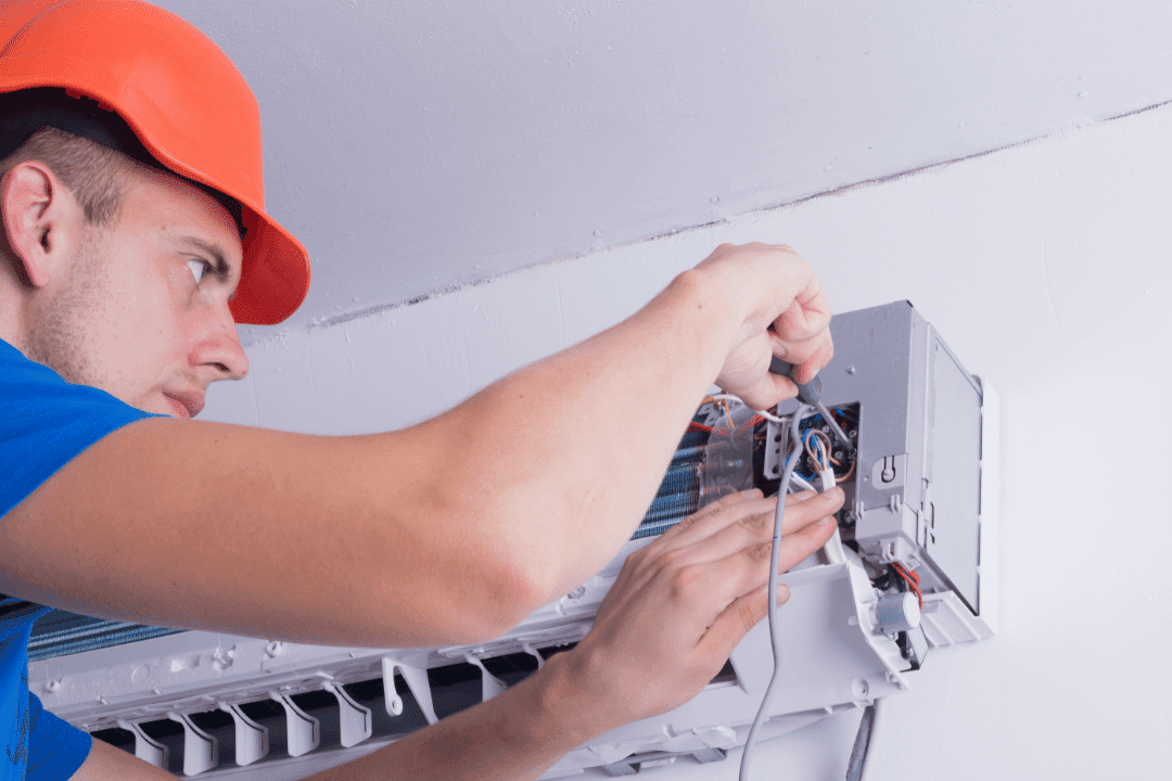 repairman orange had blue shirt installing ductless system concentrating holding screwdriver