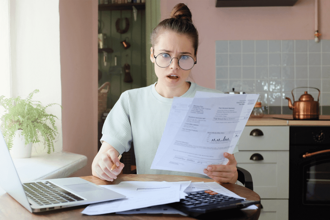 young woman shocked surprised looking at bills calculator laptop kitchen inside papers scattered