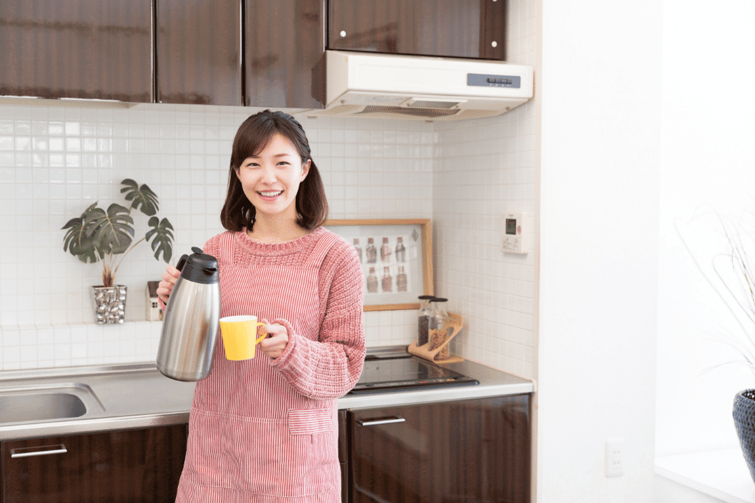 woman in kitchen pouring coffee wearing sweater smiling kitchen and thermostat in the background