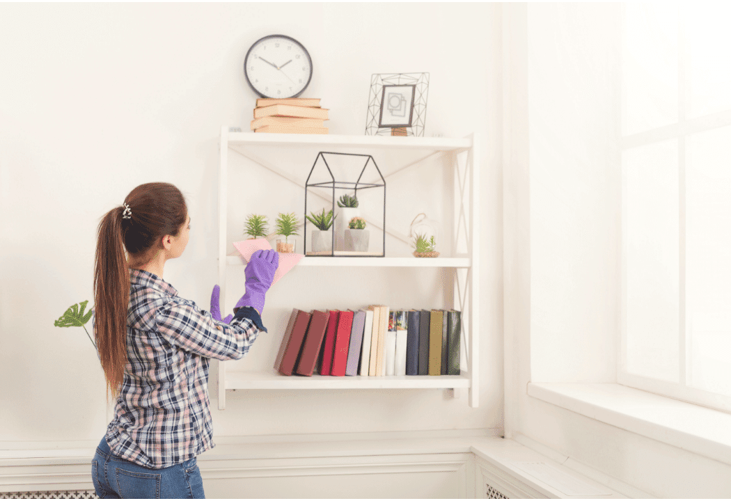 woman dusting bookshelf in living room