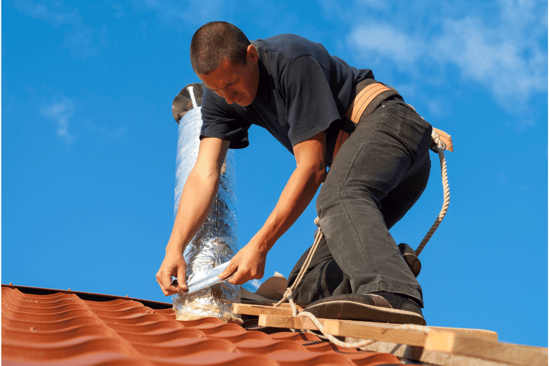 man on roof taping up a vent rope wooden platform