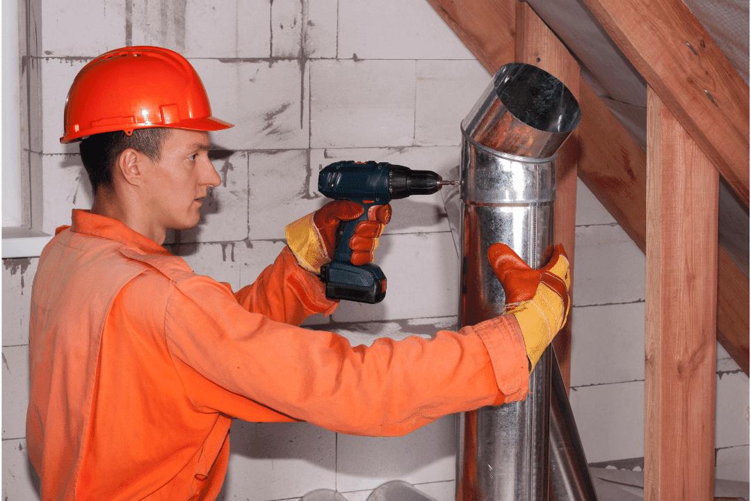 man with drill repairman drilling air vent hard hat orange