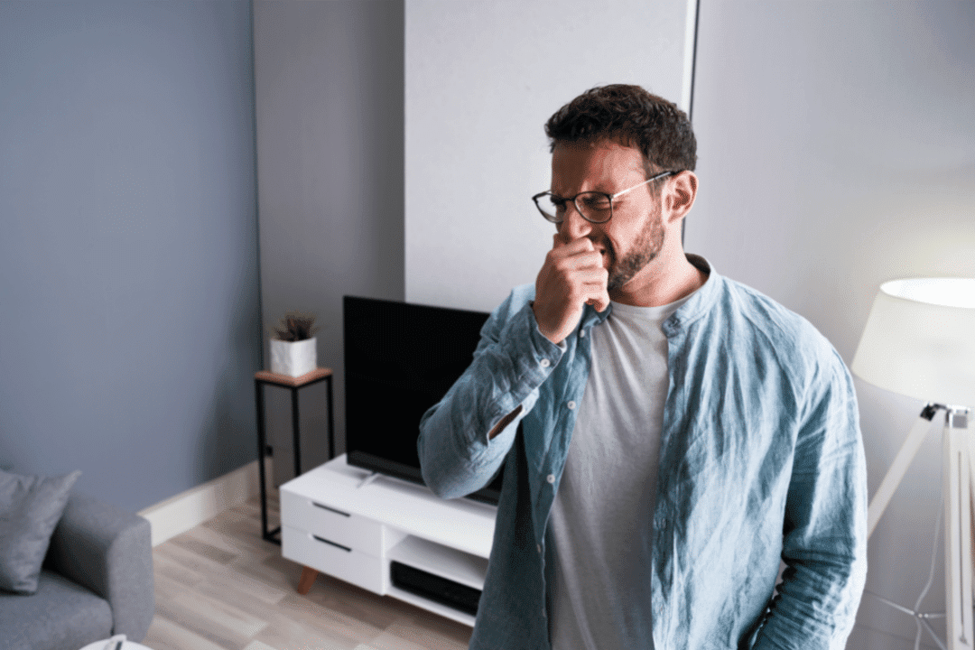 man coughing and sneezing in home living room