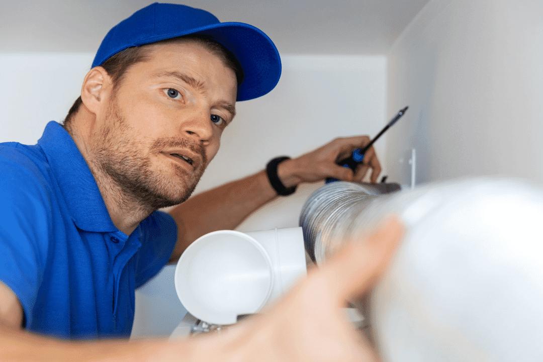 hvac repairman wearing blue installing ventilation tube in home